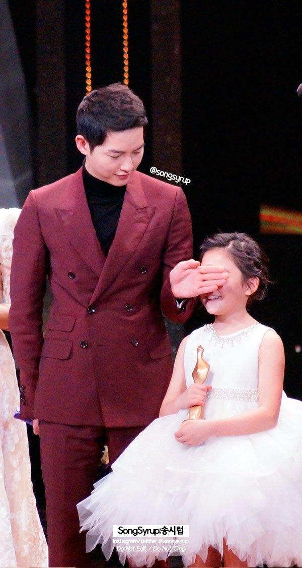 """Trong lúc màn hình công bố các nụ hôn đẹp nhất năm, Song Joong Ki đã nhanh chóng dùng tay che mắt của Heo Jung Eun. Thật đúng là một """"ông chú"""" tốt tính và đáng yêu nhất hệ Mặt Trời. Chả trách cô bé sau đó đã chọn Song Joong Ki làm diễn viên muốn hợp tác trong tương lai thay vì Park Bo Gum."""