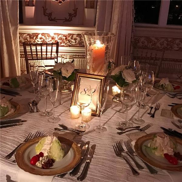 Trên bàn thì có hoa hồng và những chiếc đĩa vàng dùng cho món khai vị.