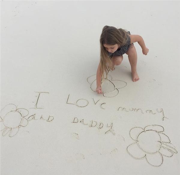 """Harper Beckham viết dòng chữ """"Con yêu mẹ và bố""""ngộ nghĩnh trên cát."""