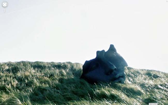Mảnh vỡ gương mặt một bức tượng nằm chỏng chơ trên một ngọn đồi