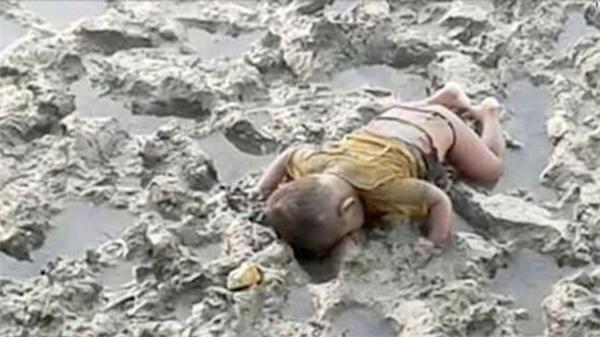 Đứa trẻ 16 tháng tuổi nằm úp mặt trên bùn cô độc và lạnh lẽo. (Ảnh: Internet)