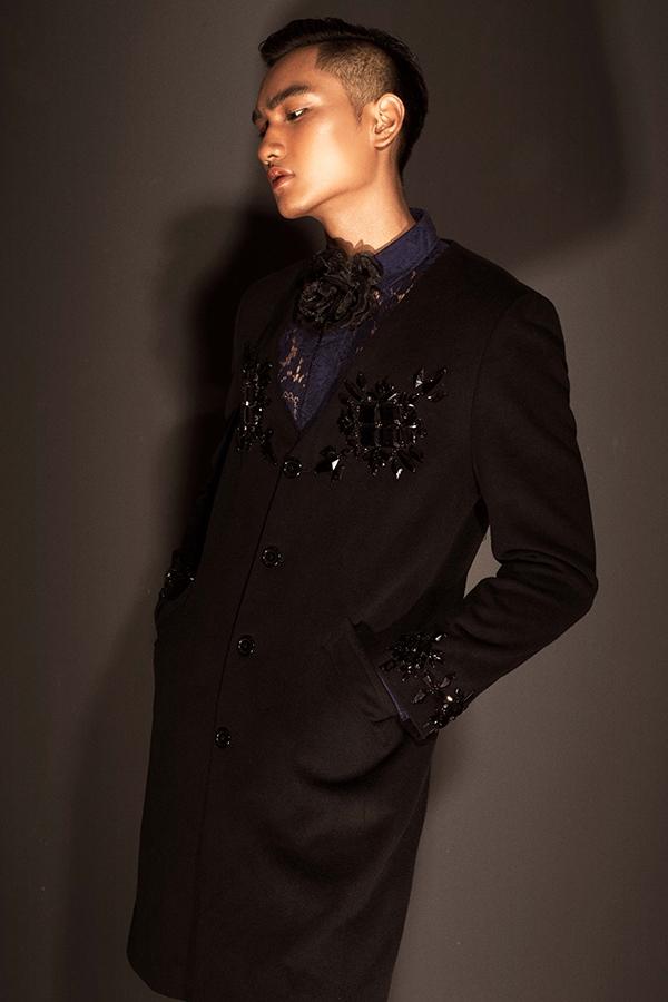 """Huy Quang lịch lãm với """"cây đen"""" được tạo điểm nhấn bằng sắc xanh trầm mặc bên trong. Chiếc áo dáng dài với phom đơn giản được Đỗ Mạnh Cường làm mới với chi tiết đính kết kì công đối xứng ở ngực, tay áo. Vẻ đẹp nam tính, mạnh mẽ của Á quân Vietnam's Next Top Model 2016 được khai thác triệt để qua những đường cắt dứt khoát, mạnh mẽ, phom dáng đơn giản."""