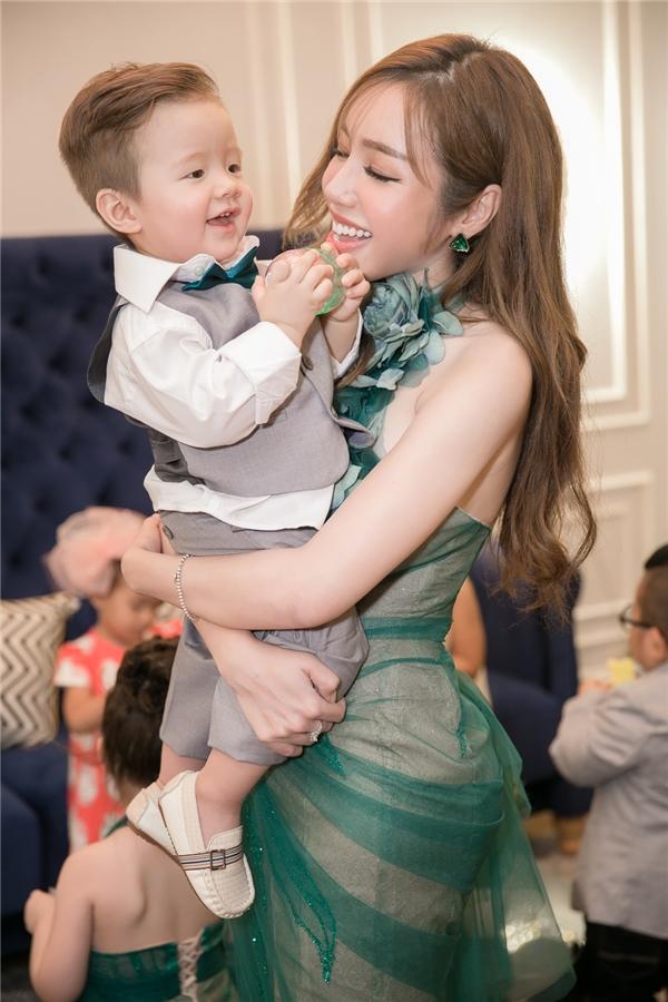 Bé Alfie Túc Mạch lại được Elly Trần cho diện suit màu xám vô cùng đáng yêu. Ba mẹ con tạo dáng đáng yêu trong không gian buổi tiệc.