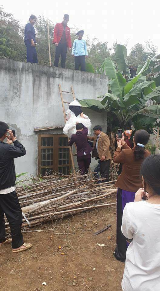 Chú rể giữ thang cho cô dâu trèo tường vào nhà...(Ảnh: Internet)