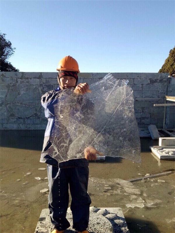 Một người dân cầm trên tay những tảng băng mỏng như tấm kính. (Ảnh:Minh Hải)