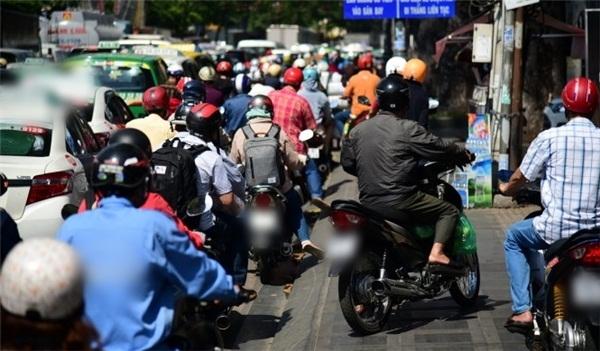 Rất nhiều xe máy đã leo lề để cố di chuyển vượt qua kẹt xe. (Ảnh: Zing)