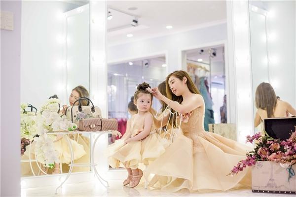 Trong hậu trường, Cadie Mộc Trà vô cùng đáng yêu trong trang phục đồng điệu với mẹ. Khi được diện váy giống mẹ, Cadie rất thích thú khi trông như một phiên bản nhí củaElly Trần.