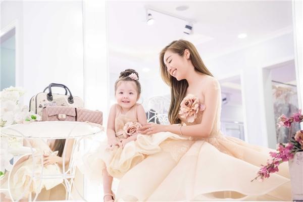 """Trong suốt quá trình chụp ảnh, Elly Trần không quên chăm sóc, quan tâm con gái. Cô tự tay chỉnh trang quần áo để Cadie có tâm trạng thoải mái, vui vẻ trong buổi chụp. Nhờ đó, """"công chúa"""" nhỏxinhluôn hào hứng thể hiện vẻ đáng yêu và những biểu cảm tự nhiên cùng mẹ."""