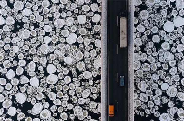 Một cây cầu bắc ngang qua một con sông bị đóng băng với những bọt khí tạo thành những vòng tròn phủ kín mặt sông.