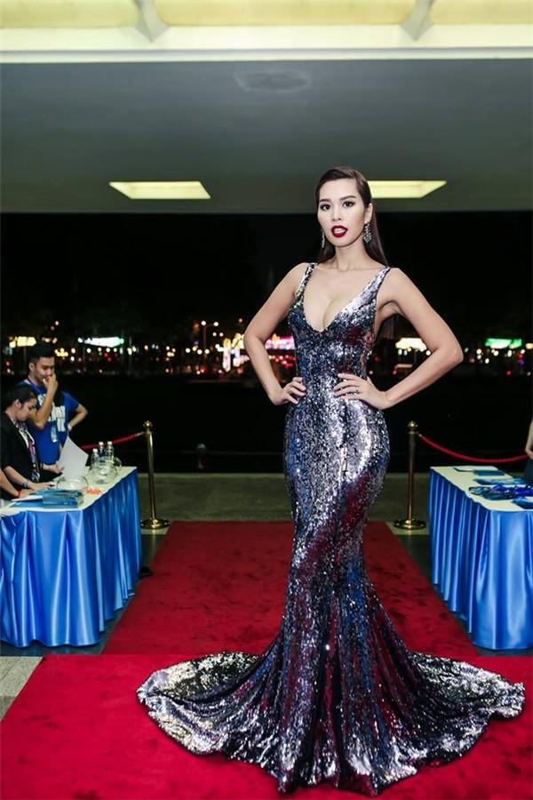Cô cũng là tâm điểm trên thảm đỏ với bộ váy đuôi cá ánh kim màu bạc bắt mắt. Thiết kế tạo điểm nhấn bởi đường xẻ ngực sâu hút phô diễn vòng một táo bạo.
