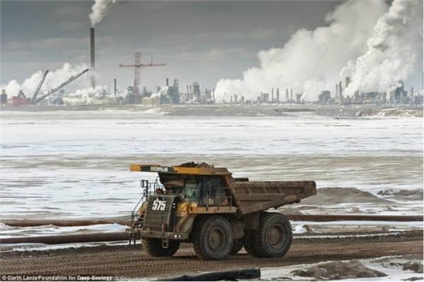 Một chiếc xe tải chở dầu cát. Xa xa là khu công nghiệp với khói thải nghi ngút trắng cả một vùng trời.