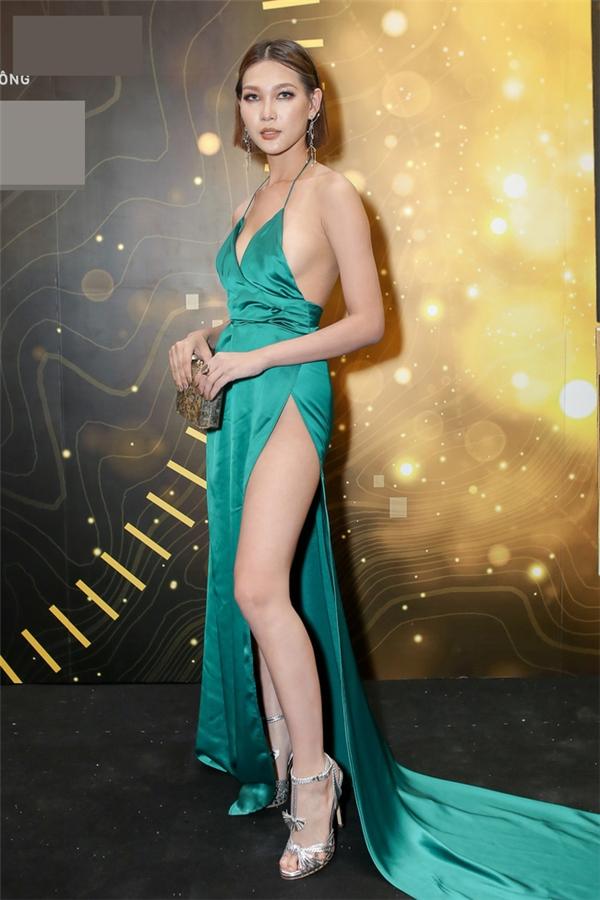 """Tối qua (12/1), sau khoảng thời gian vắng bóng, Diệp Linh Châu bất ngờ xuất hiện trở lại trong một đêm tiệc trao giải của năm. Nữ người mẫu chọn vẻ ngoài nữ tính trái hẳn với phong cách cá tính thường thấy. """"Học trò""""Phạm Hương khoe được đôi chân nuột nà trong thiết kế xẻ sâu ở phần ngực, chân váy với sắc xanh hợp- xu hướng. Tuy nhiên, ở cô nàng không toát lên được vẻ gợi cảm, quyến rũ."""