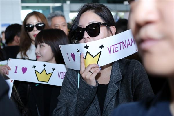 """Các cô gái thân thiện cầm băng rôn với dòng chữ """"I love Queen's Vietnam"""""""