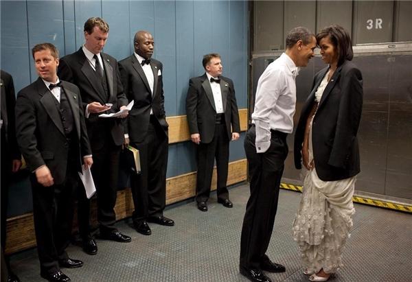 """Phút thân mật hiếm hoi của vợ chồng ông Obama khiến người xem không khỏi ngưỡng mộ. """"Không khí lúc ấy khá lạnh, vì thế Tổng thống đã khoác cho vợ chiếc áo vest ông đang mặc. Sau đó hai người đã có một chút riêng tư với nhau khi các nhân viên và đặc vụ cố gắng không nhìn"""", nhiếp ảnh gia Nhà TrắngPete Souza kể lại."""