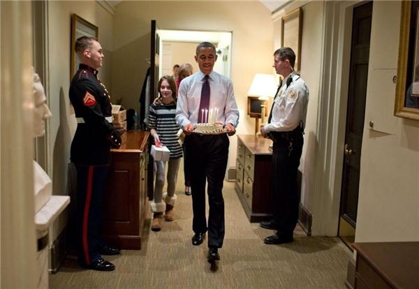 Ông Obama cùng con gái của Chánh Văn phòng Denis McDonough mang chiếc bánh kem để tổ chức sinh nhật bất ngờ cho ông này tại văn phòng cánh Tây Nhà Trắng.