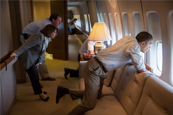 Tổng thống Obama nhìn ra ngoài cửa sổ máy bay để quan sát những hậu quả của một cơn bão cùng với những nhân viên của mình trong lúc chiếc Air Force One đang hạ cánh xuống căn cứ không quân Tinker tại bang Oklahoma, .