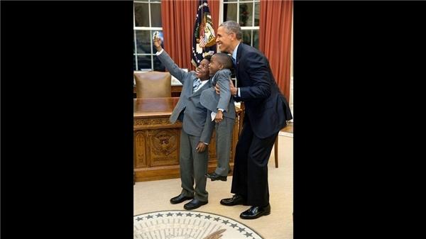 Tổng thống Obama đang bế cậu bé James Haynes (4 tuổi) lên đang được để cùng ông chụp ảnh selfie với anh trai cậu, Jacob Haynes (11 tuổi).