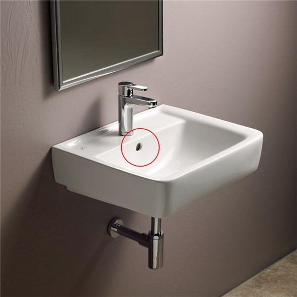 Chiếc lỗ nằm trên thành bồn rửa mặt chính là lỗ thoát nước thứ hai, nó ăn thông với ống dẫn nước nằm ngay phía dưới bồn rửa. Trong trường hợp bạn đậy nắp bồn lại mà quên tắt vòi nước thì chiếc lỗ này sẽ giúp nước thoát xuống cống chứ không tràn ra nhà.