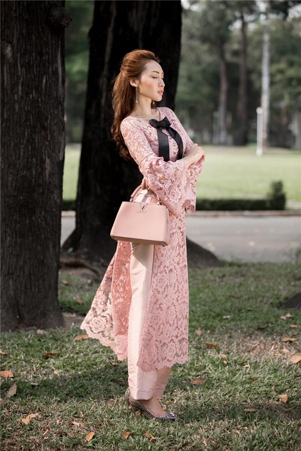 Nữ người mẫu khoe dáng trong thiết kế màu hồng phấn ngọt ngào kết hợp giữa áo ren cùng quần taffta mềm mại. Bộ cánh được tạo điểm nhấn bằng chiếc nơ đen to bản.