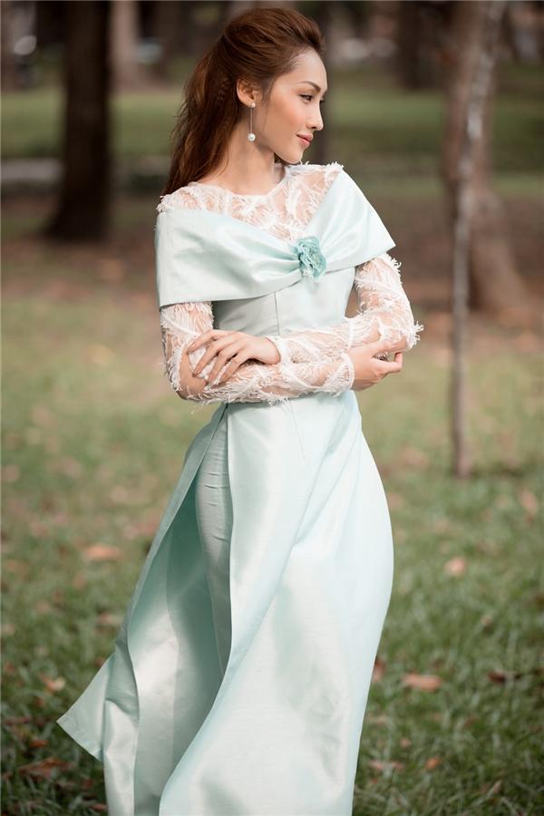 Bộ áo dài nơ quàng vai với tông màu xanh nhạt cổ điển, duyên dáng, quyến rũ pha chút đơn sơ mộc mạc sẽ khiến các cô gái xiêu lòng.