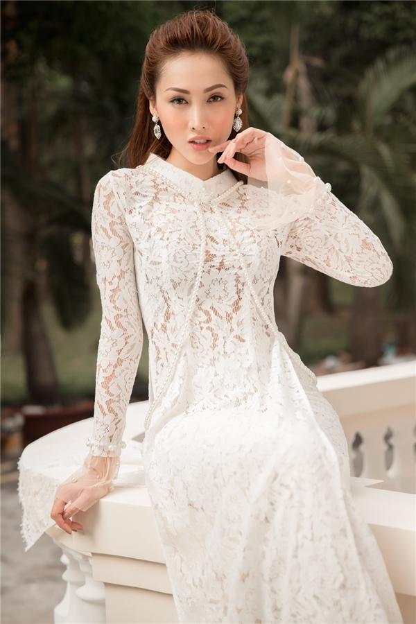 Phần vải quàng vai như chiếc khăn choàng mang đến sự sang trọng, quý phái cho người phụ nữ. Chất ren chỉ trắng ôm gọn bờ vai và dọc theo cánh tay tạo nên nét khả ái cho người mặc.