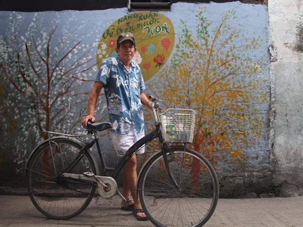 Ông Minh cùng chiếc xe đạp chở đầy màu sơn của mình.