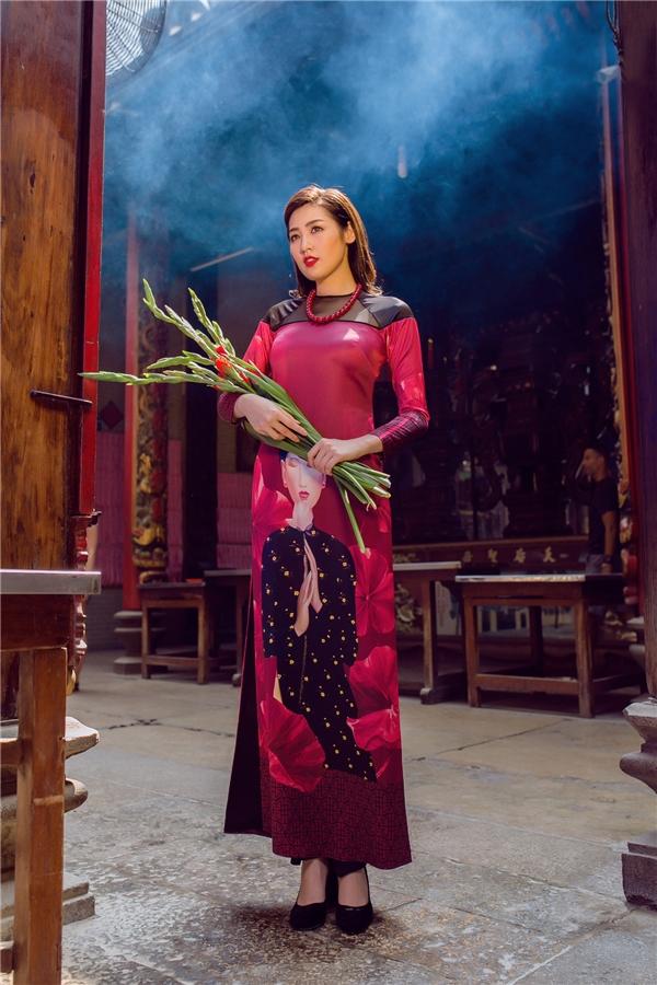 Trong không gian cổ kính, thoảng đượm hương Xuân, Tú Anh đẹp như tranh vẽ với thiết kế màu hồng thẫm, họa tiết người phụ nữ Việt xưa được in kĩ thuật số to bản ngay giữa tà áo.
