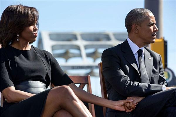 """Tổng thống và Đệ nhất phu nhân nắm tay nhau khi lắng nghe những nhận xét của đại diện John Lewis trong lễ tưởng niệm lần thứ 50 của """"Ngày chủ nhật đẫm máu"""" tại Montgomery, ngày 7/3/2015."""