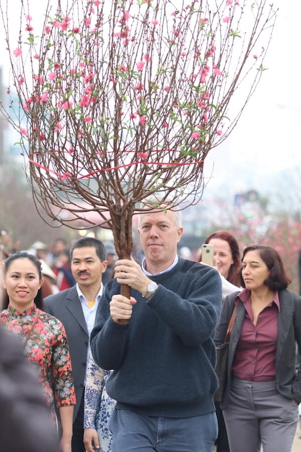 Ngay sau đó, Đại sứ Mỹ cùng những người bạn của mình cùng đi chợ hoa Quảng An, chọn mua đào để trang trí cho Tết.