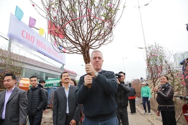 Ông dừng lại mua một cành đào với giá 600.000 đồng. Đại sứ vui vẻ chụp ảnh và trò chuyện với người bán hàng.