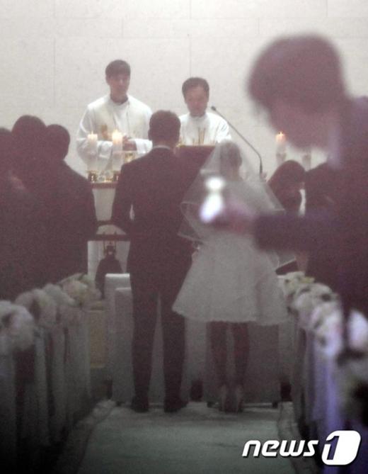 Hình ảnh cô dâu chú rể trong lễ đường được hé lộ. Tuy hơi mờ, nhưng cũng đủ để thấy được đôi thân thon thả của cô nàng Kim Tae Hee đang đứng cạnh chú rể Bi Rain vô cùng xứng đôi.