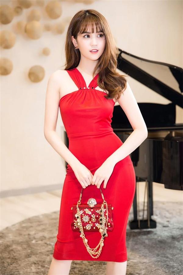 Ngọc Trinh sử dụng túi hiện đắt đỏ phối cùng trang phục đồng điệu. Làn da trắng hồng của nữ người mẫu được tôn lên tuyệt đối nhờ sắc đỏ may mắn đặc trưng cho ngày đầu Xuân.