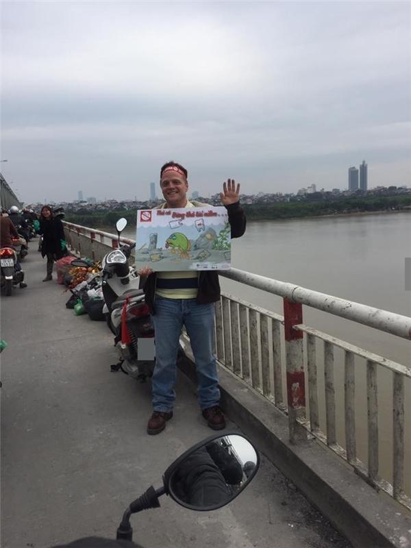 """Hình ảnh anh Tây trên cầu Chương Dương với tấm biển """"Thả cá đừng thả túi nilon"""" khiến nhiều người chú ý.(Ảnh: Internet)"""