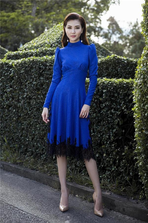Màu xanh cobant trẻ trung được kết hợp cùng ren đen ở phần chân váy lạ mắt. Thiết kế mang đậm phong cách thời trang cổ điển bởi sự kín đáo, thanh lịch cùng chi tiết tay phồng, cổ đứng đặc trưng.