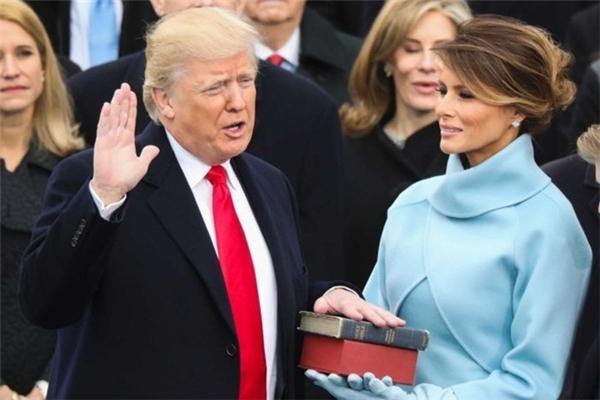 Donald Trump đặt tay lên quyển kinh thánh tuyên thệ nhậm chức Tổng thống Mỹ đời thứ 45. Người cầm cuốn sách là vợ của ông, bàMelania Trump. (Ảnh: internet)