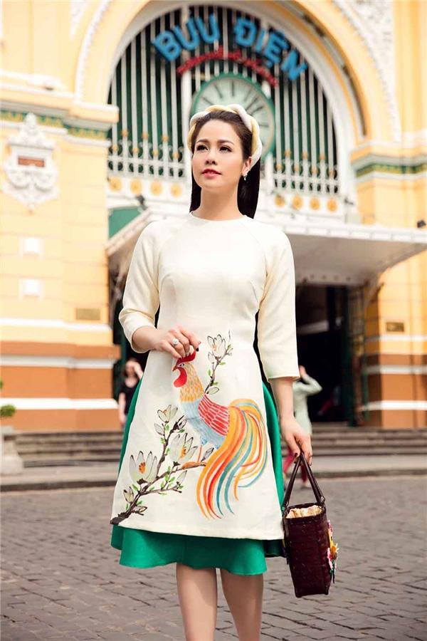 Nữ ca sĩ trẻ trung với áo trên gối kết hợp váy lụa ngắn màu xanh thẫm bắt mắt. Bộ trang phục được tạo điểm nhấn bằng họa tiết gà trống - linh vật của năm 2017 này.