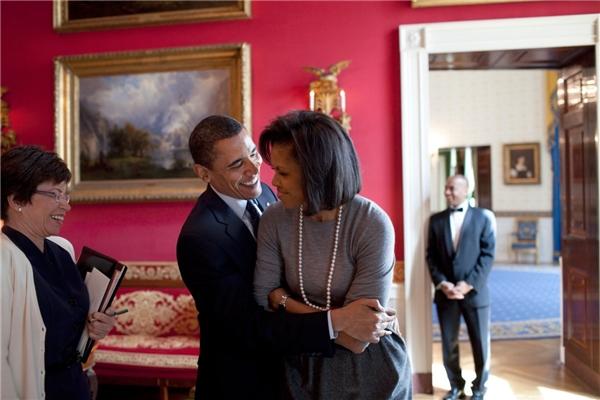 Âu yếm vợ trước sự có mặt của Cố vấn Valerie Jarrett trong Phòng đỏ tại Nhà trắng.