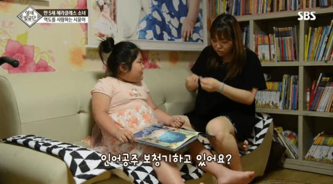 Mẹ của bé đang chuẩn bị máy trợ thính cho con gái.