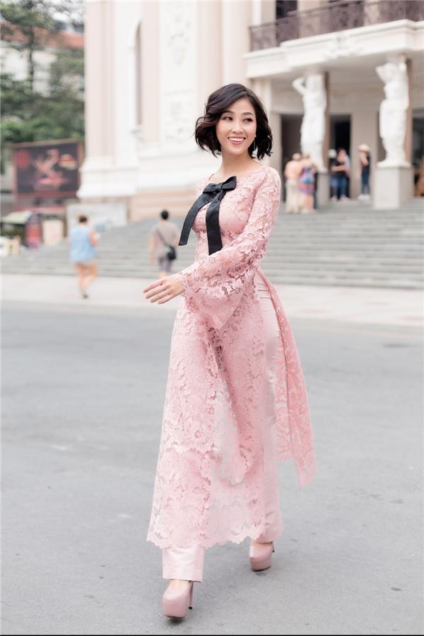 """Hari Won, Tô Uyên Khánh Ngọc và Liêu Hà Trinh """"đụng hàng"""" chiếc áo dài màu hồng ngọt ngào trên nền chất liệu ren lưới mỏng manh kết hợp quần đồng điệu màu sắc. Bộ cánh được nhấn nhá bằng thắt nơ to bản màu đen tương phản. Phom dáng gọn nhẹ của thiết kế này được phái đẹp ưa chuộng trong mùa Tết 2017 bởi tính ứng dụng cao, thoải mái di chuyển."""