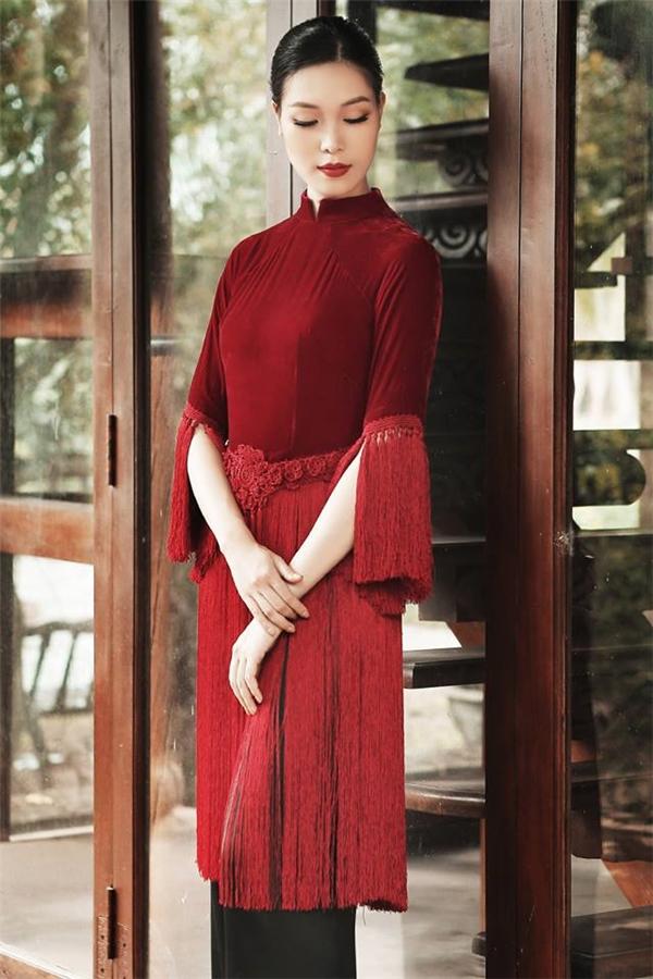 Bộ áo dài với chất liệu nhung, sắc đỏ rượu nồng nàn, quyến rũ của Hoa hậu Thùy Dung được cách tân mới mẻ với phom mini nhỏ xinh cùng chi tiết tua rua mềm mại, uyển chuyển.