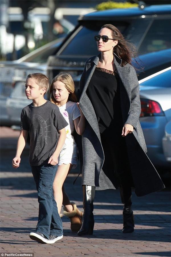 Knox thì rảo bước đi trước mẹ và chị trong trang phục quần jeans áo thun tối màu đơn giản. Cô chị Vivienne thì mặc short trắng và áo thun họa tiết màu trắng, luôn nắm chặt tay mẹ.