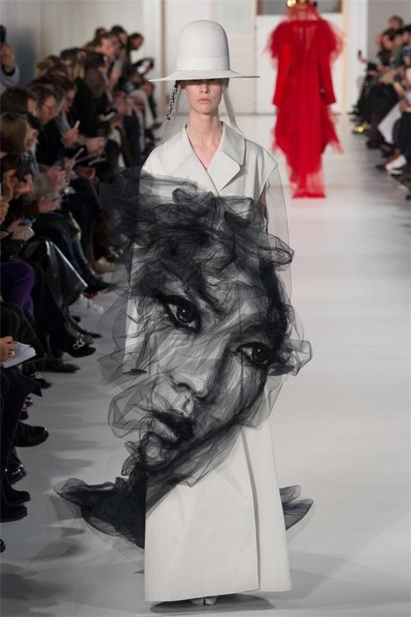 Trong số 27 thiết kế mới của John Galliano, điều khiến khán giả, giới mộ điệu chú ý nhất là chiếc áo khoác dáng dài chạm gối có hình mặt người được khắc họa bằng vải voan trông như sương khói.