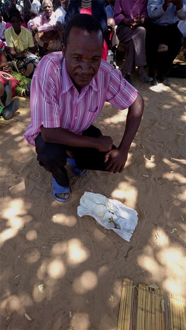 Anh Nomore đem xác con đi thiêu trước sự chứng kiến của dân làng.