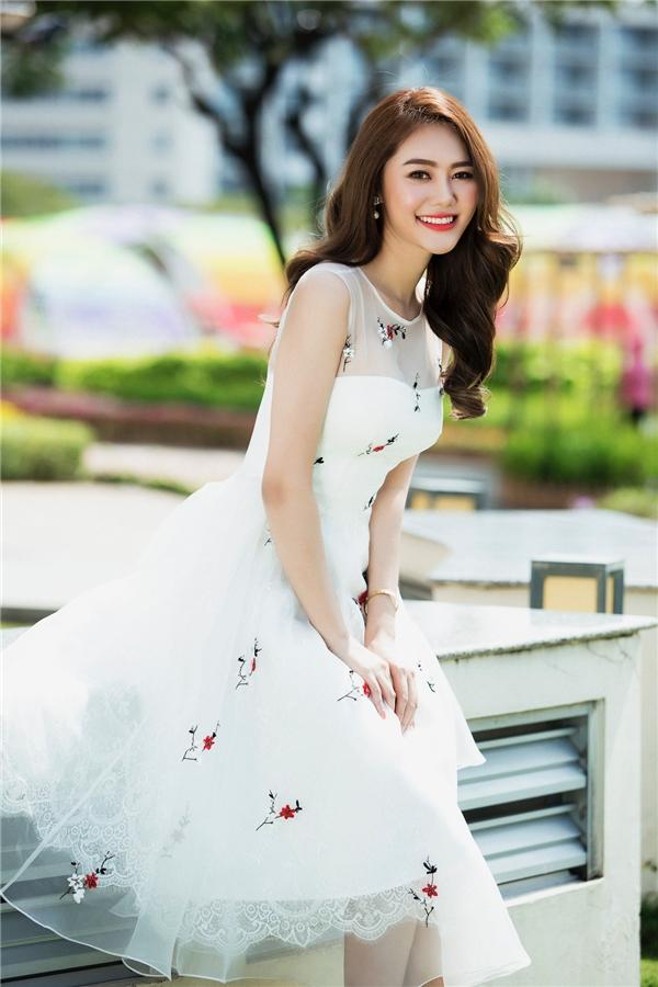 Linh Chi như nàng công chúa bước ra từ thế giới cổ tích với chiếc váy trắng xòe ngang gối kết hợp họa tiết hoa màu đỏ nổi bật, thu hút của nhà thiết kế Đỗ Long.