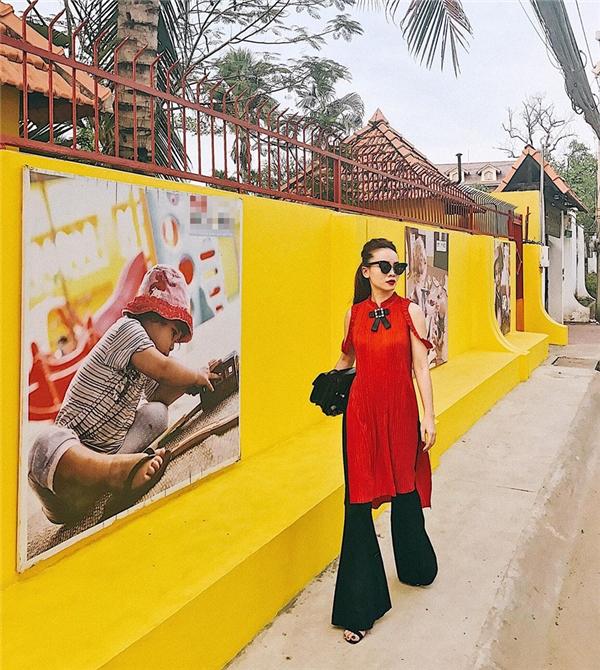 Dư âm của những ngày Tết vẫn còn đọng lại trên bộ cánh của Yến Trang khi kết hợp áo dài cách tân màu đỏ rực rỡ cùng quần dài ống loe lạ mắt.