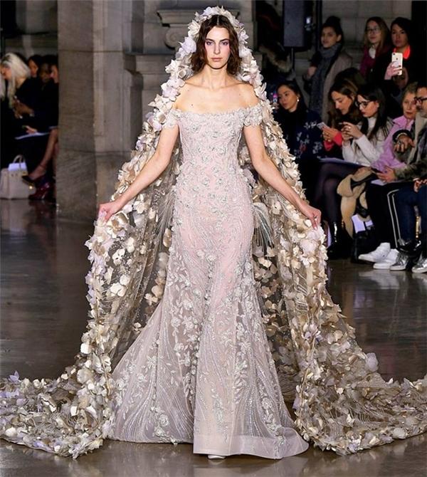 Georges Hobeika khiến người xem không khỏi choáng ngợp với phom váy đuôi cá kết hợp khăn choàng đầu quá đỗi kì công. Nếu mang ra đời thực, một chiếc khăn voan mềm mại đồng điệu màu váy đã đủ giúp trở nên lộng lẫy.