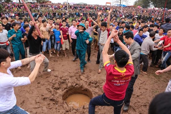 Đúng 15g, chủ tế bắt đầu rước phết từ đình làng đến bãi đất trống nơi hàng nghìn người đang chờ đợi, tiếng reo hò mỗi lúc một lớn khi chủ tế bắt đầu chôn quả phết xuống đất.