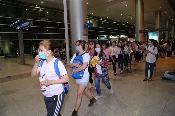 Fan xếp hàng ngay ngắn di chuyển qua cổng VIP của sân bay để chuẩn bị đón thần tượng.