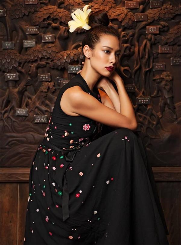 Bộ váy màu đen cổ điển được nhấn nhá bằng loạt họa tiết hoa nổi bật, mềm mại với hai tông trắng, đỏ làm chủ đạo.