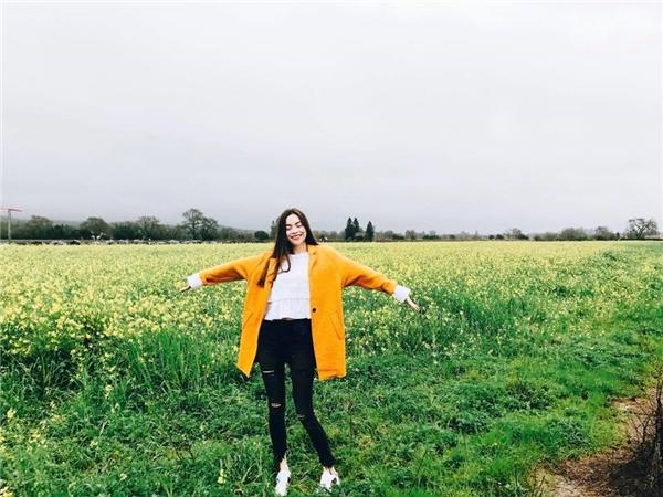 Giữa cánh đồng hoa cỏ trên đất Mỹ, Hồ Ngọc Hà cuốn hút với áo khoác màu vàng cam kết hợp cùng quần jeans rách cá tính, áo màu trắng nhẹ nhàng, đơn giản.